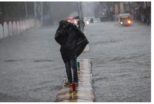 Un hombre está parado en un divisor de carreteras en una calle inundada durante las lluvias monzónicas Jammu, India, el lunes 12 de julio de 2021. La temporada de monzones de la India va de junio a septiembre. (Foto AP / Channi Anand)